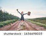 Small photo of happy romantic girl travels on the road with a suitcase. woman in a blooper and with a bouquet of color joyful raised her hands up. concept vacation, freedom