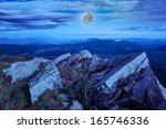 rocky ledge at the top mountain slope at night - stock photo