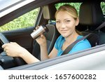 Small photo of Woman as a driver is drinking coffee during a car ride and is therefore careless and distracted