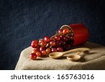 Red grapes in a tin on table, still life - stock photo