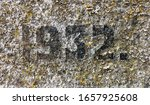 """1932"" chiselled out of granite and polished – a detail of an inscription produced that year. Profusely covered with lichen"