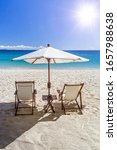 Small photo of Two deckchairs and a sunshade on the beach facing the sun