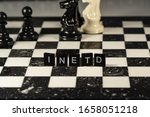 Small photo of Inetd short for (unix/linux) Internet Service Daemon represented by black and white letter tiles on a marble chessboard with chess pieces