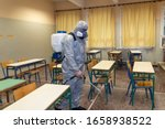 Thessaloniki, Greece - Feb 28, 2020: Workers sprays disinfectant as part of preventive measures against the spread of the COVID-19, the novel coronavirus, in a school  - stock photo