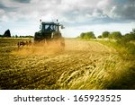 Tractor Ploughing A Field With...