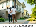 Small photo of Beautiful family portrait smiling outside their new house with sunset, this photo canuse for family, father, mother and home concept