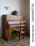 An Antique Organ With Chair On...