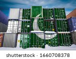 The national flag of Pakistan on a large number of metal containers for storing goods stacked in rows on top of each other. Conception of storage of goods by importers, exporters