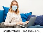 Young business woman working from home with laptop, wearing protective mask - stock photo