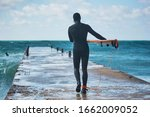Surfer Is Walking On Pier And...