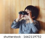 Portrait of kid boy child looking through of binoculars in the animals station view point, A young explorer with wildlife nature in summer camp - stock photo