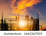 Silhouette of Engineer and worker on building site, construction site with clipping path at sunset in evening time. - stock photo