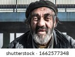 Small photo of Close up portrait of old homeless alcoholic man face with white beard and hair wandering on the street depressed sick and lonely, social issues homelessness documentary concept