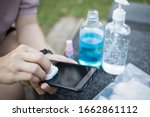 Small photo of Cleaning mobile phone to eliminate germs,Covid-19 hands of asian woman cleaning the phone by hand sanitizer gel,girl using cotton wool with alcohol to wipe to avoid contaminating with Corona virus