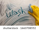 Small photo of Hand washes washes a mirror with soap. The inscription on the soap glass - wash