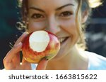 Young Woman Holding Apple With...