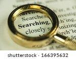 Macro Image Of A Magnifying Glass Over The Word Searching In A Dictionary - stock photo