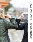 Small photo of Elbow bump. New greeting to avoid the spread of coronavirus. Two women friends meet in British street with bare hands. Instead of greeting with a hug or handshake, they bump elbows instead. Vertical.