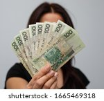 close up of several banknotes with a face value of PLN 100 Polish money, zloty held in a fan shape in the hands of a women on a grey background - stock photo