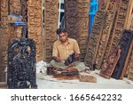 Small photo of Saras Mela, Kolkata. 03/01/2020: A woodcraft artisan polishing a small wooden burst, for sale in the fair. Large panels of exquisitely detailed wood panels of classical Indian design elements are seen