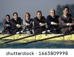 Team of rowers in business suits