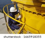 Small photo of greasing hose connected to ship crane slewing during routine lubricating by ship crew.