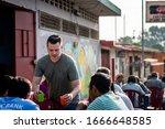 Small photo of Santa Rosa Guatemala 01-20-2020 caucasian missionary feeding the homeless in Guatemalan village