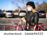 A young woman wears an N95 respirator while leaning on a shopping cart outside of a grocery store. The woman is protecting herself from coronavirus and other airborne particles and diseases.