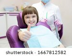 Small photo of Kid sitting in dental chair. Little girl patient showing thumb-up approving pediatric dental service in modern clinic for children. Focus on happy smiling positively child. Good oral dent health