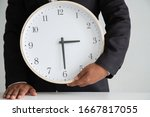 Small photo of Businessman holding a clock ready to work Strategy and time management in the office,Concept: symbol manage at deadline professional for success, Time to take a summer vacation, manager hour job