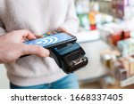 Small photo of The seller holds a payment terminal, and the man pays for the purchase using a smartphone, online. On the phone screen-wi-fi network. NFC concept, business and banking operations.