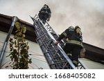 Firefighters On Ladders In...
