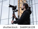 Young Professional videographer holding professional camera on 3-axis gimbal stabilizer. Pro equipment helps to make high quality video without shaking. Cameraman wearing white hoodie making a videos. - stock photo