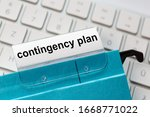 Small photo of contingency plan is on a label of a blue hanging file. In the background a computer keyboard