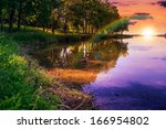 Mountain lake and forest on the embankment in evening - stock photo