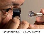 Small photo of Close up jeweller asian man looking through loupe polished diamond. Diamond view. Diamonds grading.