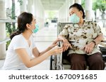 Small photo of Young Asian grandchild taking care her grandmother sitting on wheelchair. Grandmother almost 90 years old was take care by her granddaughter while traveling at park. People wearing protective mask.