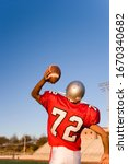 Small photo of American football player throwing ball during game