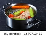 Small photo of slow-cooked fish broth or soup of salmon, onion, carrot, celery, herbs and spices in a stockpot on a concrete table, horizontal view from above, close-up