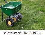 A  seed  and  fertilizer spreader out on a lawn