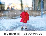 Small photo of Outdoor winter portrait of little cute toddler girl in red coat and white fashion hat barret. Healthy happy baby child walking in the park on cold day with snow and snowfall. Stylish clothes for kids