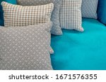 Small photo of Middle size puffy pillows with patterned upholstery in gray, beige and brown colors lying one after the other on the light blue fabric upholstery of the sofa. Abstract interior design background.