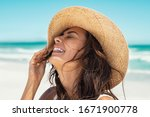 Small photo of Close up face of young stylish woman wearing straw hat at beach. Happy tanned latin woman laughing during summer holiday. Beautiful fashionable girl relaxing at beach while holding large brim for wind