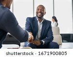 Small photo of Two happy mature business men shaking hands in office. Successful african american businessman in formal clothing closing deal with handshake. Multiethnic businessmen shaking hands during a meeting.