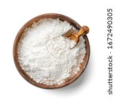 Small photo of Wooden bowl with flour and flour spoon. Rice or wheat flour isolated on white background. top view
