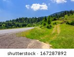 Empty asphalt mountain road with Painted single white Line near the coniferous forest with cloudy sky in morning light - stock photo