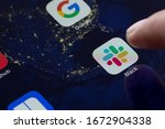 Small photo of Portland, OR, USA - Mar 14, 2020: Closeup of Slack mobile app icon on an iPad and a finger opening it. Slack is a B2B software, workplace messenger, team communication tool or platform.