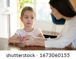 Small photo of Head shot unhappy small child girl sitting at table with worrying mother, sharing school problems. Compassionate caring attentive mommy having trustful conversation with unhappy offended daughter.