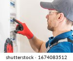 Professional Electric Technician Installing Main Fuses Box Inside Newly Developed House. Residential Electrical System. Industrial Theme. - stock photo