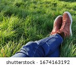 Mans legs in blue jeans and brown leather boots on the green lawn in a sunny summer day